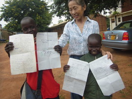 K.Hatsue known locally as Lamunu,PRAfrica country director with some of the children she is helping.