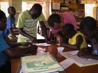 学校長期休暇中、大勢の一般ユーザーでごった返す中、支援者に送る手紙を書く子ども達をヘルプ中のRobinsonとOgen So。