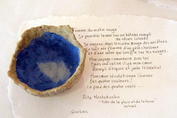 Coupe du Quebec constituée de sable et de papier avec un extrait de poème de Rita Metsokosho