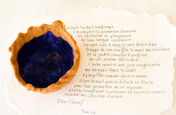 Coupe de Tunisie constituée de sable et de papier avec un extrait de poème d'Ibn Charaf