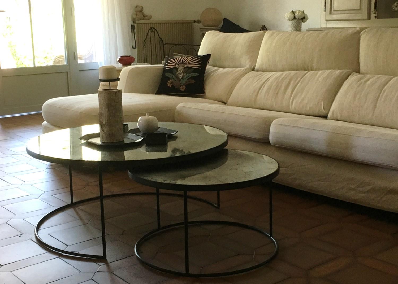Mise en lumière d'un grand séjour de style provençal. Camaïeu de couleurs douces, tables gigognes en verre et métal et canapé en lin.