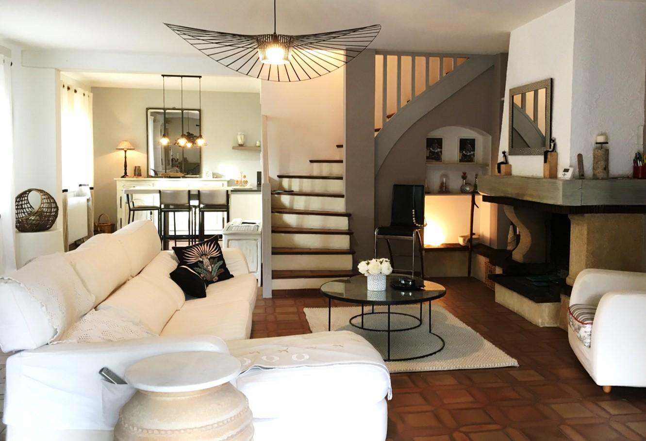 Mise en lumière d'un grand séjour de style provençal. Camaïeu de couleurs douces, suspension Vertigo, tables gigognes en verre et métal, rideaux et canapé en lin.