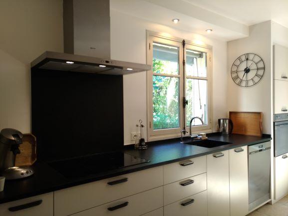 Conception d'une cuisine contemporaine avec plan et crédence en granit noir flammé et portes laquées couleur lin satiné