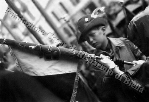 Mario Cucco, nipote dell'omonimo tenente alpino caduto ai Solaroli, sorregge il vessillo del battaglione biellese (Fondazione Cassa di Risparmio di Biella,archivio Cesare Valerio)