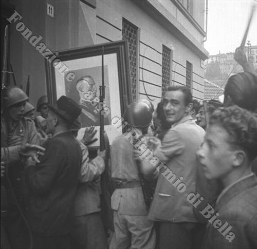 Dopo l'irruzione nella Casa del Fascio alcuni manifestanti scendono in strada innalzando il ritratto di Vittorio Emanuele III (Fondazione Cassa di Risparmio di Biella, archivio Cesare Valerio)