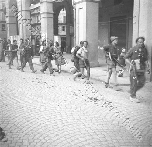 """Partigiani del battaglione """"Talpa"""" in piazza Vittorio Veneto, 24 aprile 1945 (Fondazione Cassa di Risparmio di Biella, archivio Cesare Valerio)"""