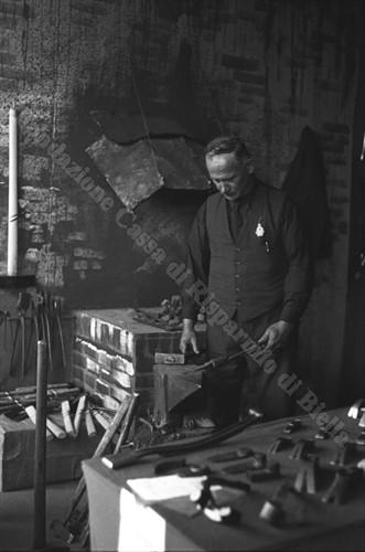 Un artigiano esperto nella lavorazione del ferro all'opera durante la I Mostra dell'Artigianato Rurale e Alpigiano del 1936 (Fondazione Cassa di Risparmio di Biella, archivio Cesare Valerio)
