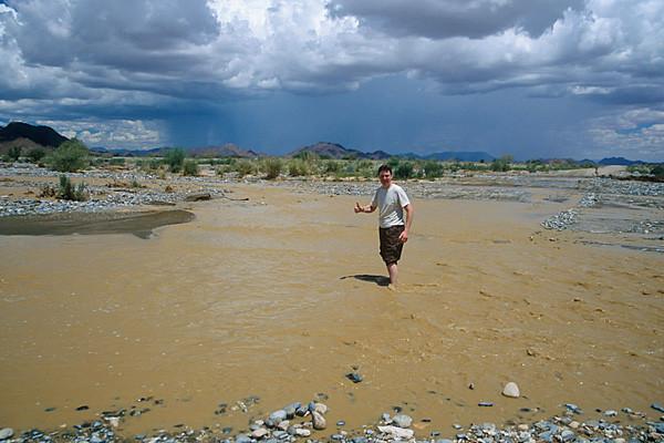 """Der Tsauchab hat die Straße überflutet, Hartmut überprüft die Wassertiefe auf der C27: """"alles ok, wir können durchfahren""""."""