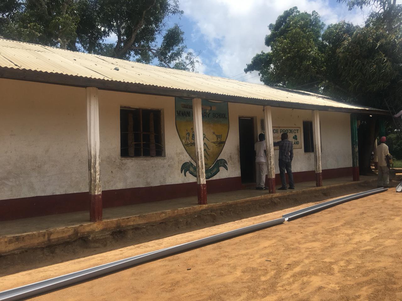 Die Wasserrinnen werden am Schulgebäude angebracht