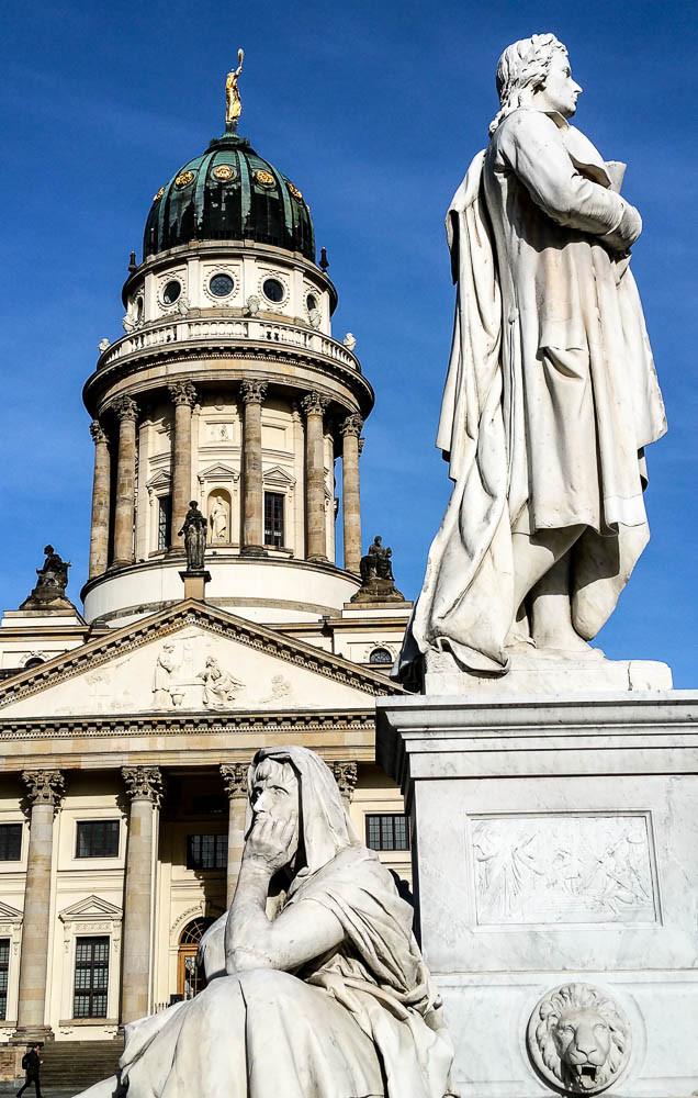 """Schillerdenkmal mit einer allegorischen Frauenfigur zur """"Philosophie"""" auf dem Gendarmenmarkt. Im Hintergrund der Französische Dom"""