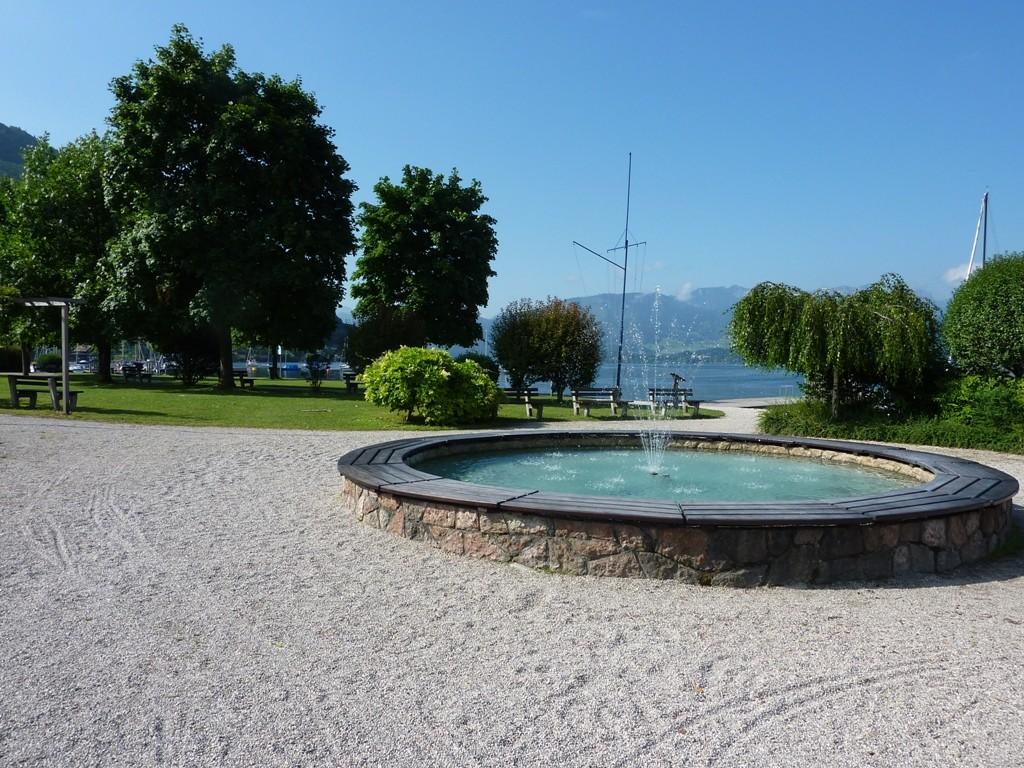 Zugang zum öffentlichen Badeplatz mit Springbrunnen, Liegewiese und Steg