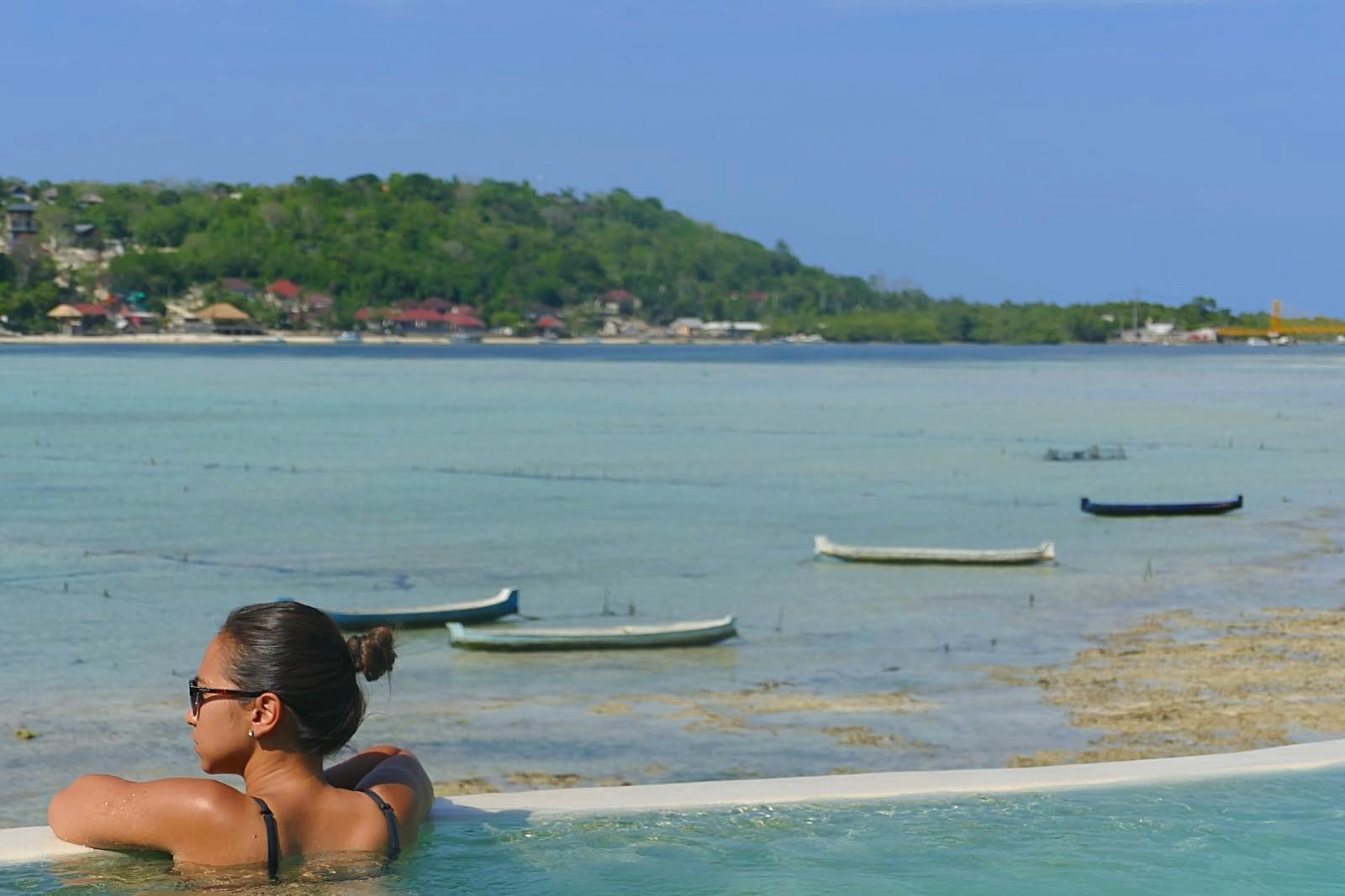 Mit einem Drink habt ihr auch das Eintrittsticket zu den coolen Pools - im Hintergrund seht ihr Nusa Lembongan mit der Yellow Bridge