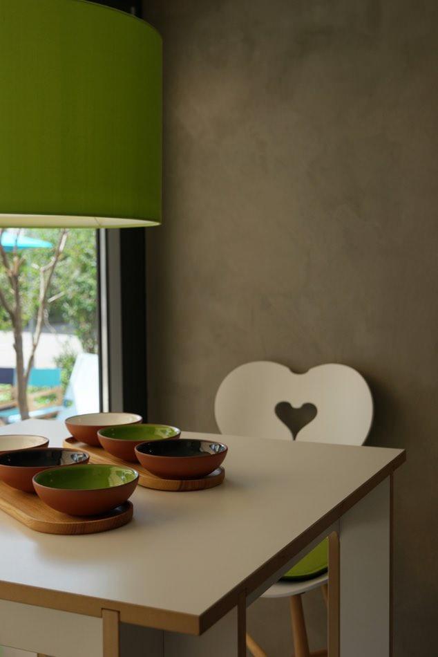 Liebevoll grünes Stilleben: Möbel mit fugenlosem Wandbelag in Betonoptik