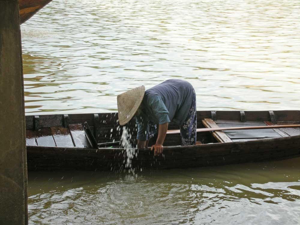 Sie schöpft Wasser aus dem Boot