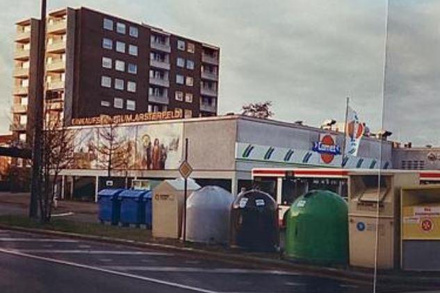 """Unter dem Schriftzug """"Einkaufszentrum Arsterfeld"""" am damaligen """"Comet""""-Markt ist das Kunstwerk Obervielander Vergangenheit und Gegenwart aus dem Jahr 1983 zu sehen. Das Wandbild erstreckt sich auf einer Fläche von 4 x 15 Metern. (Foto: 1994, Anwohner)"""