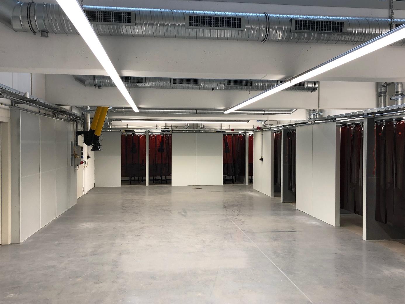 Schallgedämmte Schweißerkabinen (links, Vorführplatz, Schweißen mit Schallschutzwand)