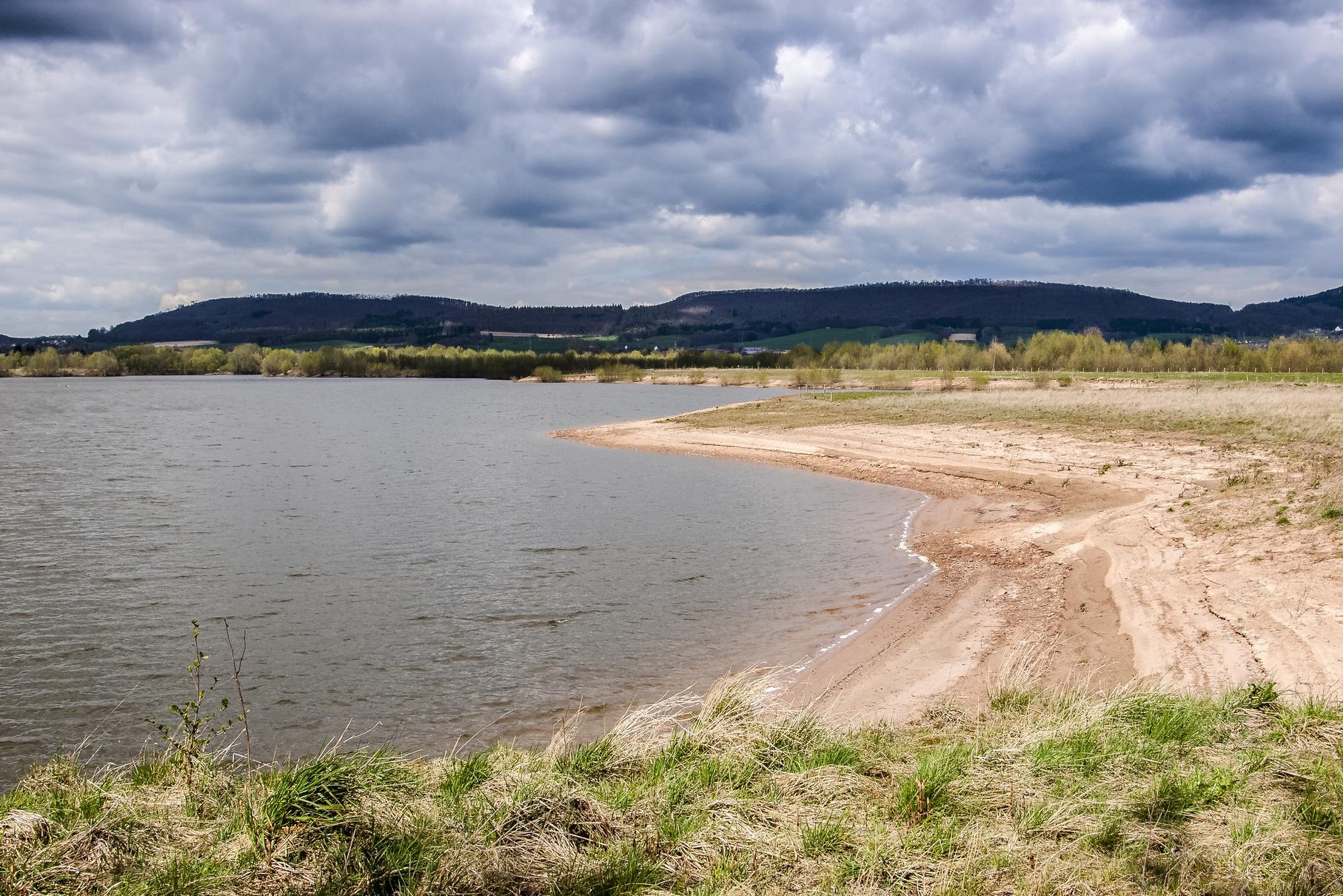Dunkle Wolken über den Kiesteichen des Naturschutzgebietes.