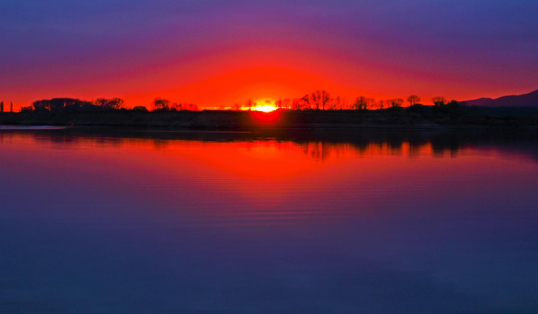 Sonnenuntergang am westlichen Teich der Auenlandschaft.