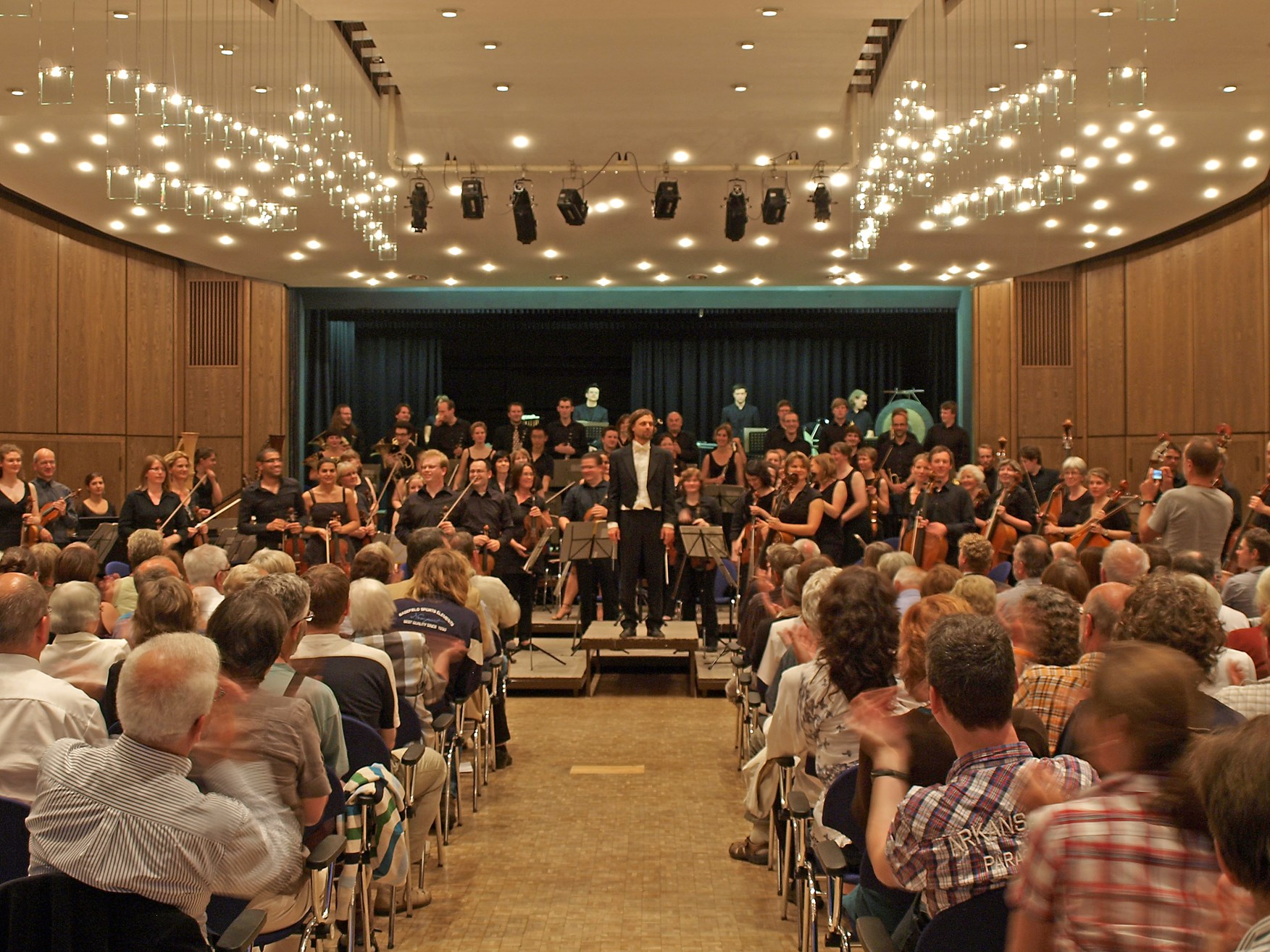 Der Dirigent mit dem Orchester nach dem Konzert. - Foto: Kathy Büscher