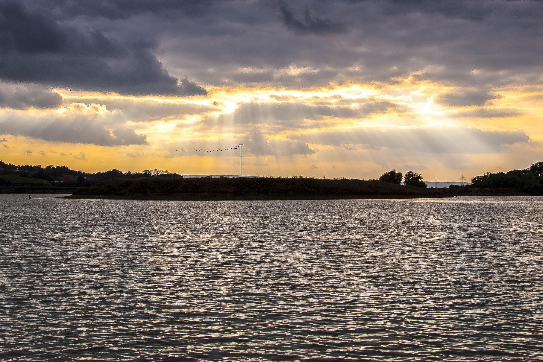 Lichtstrahlen am düsteren Himmel über der Vogelinsel.