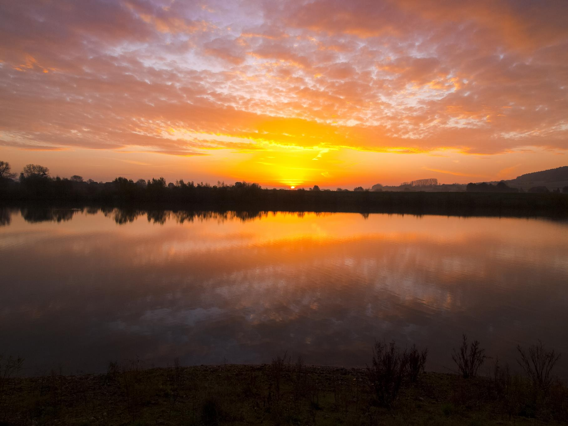 Sonnenaufgang mit Wolkenreflexion am östlichen Teich.