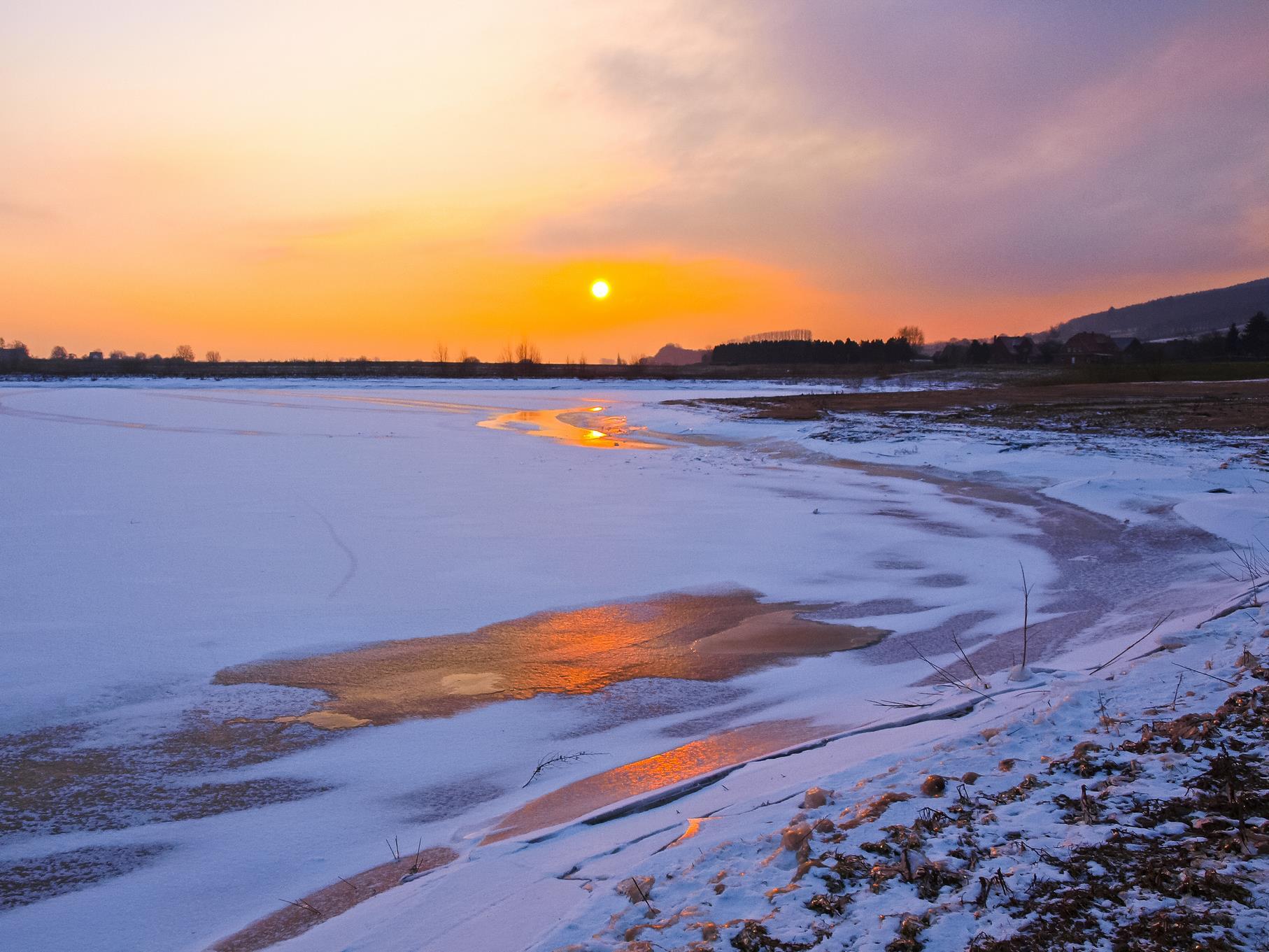 Sonnenaufgang am mittleren Teich über dem verschneiten und vereisten Wasser.