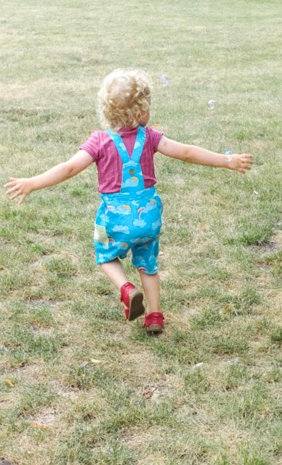 Kindergartenkind mit bunter Latzhose und T- Shirt in beere  in Bio-Qualität