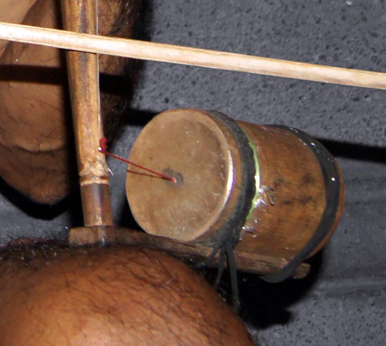 Résonateur en bambou sur lequel est fixé un film plastique. Un fil est tendu entre la base de la corde et le centre de la membrane.