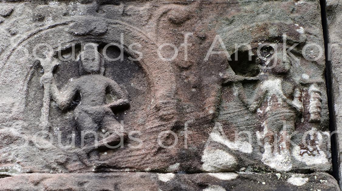 Porteur de deux arbres à cloches sur une palanche devant un ascète portant le trident de Shiva. Original. Preah Khan d'Angkor.