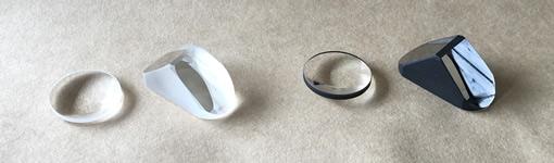 左は普通のレンズとプリズム。右は使われない部分を黒く塗ったレンズとプリズム。根気の必要な作業だが、内面の乱反射の抑制に大きな効果がある。
