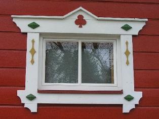 Holzhaus in Blockbauweise mit weißen Fensterrahmen