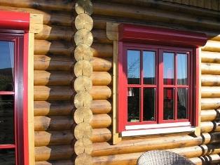 Rundbohlenhaus mit roten Fensterrahmen