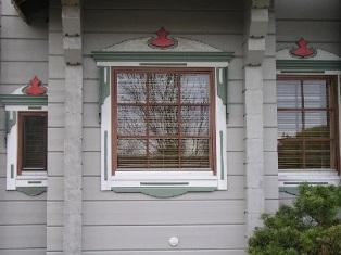 Massivholzhaus mit weißen Fensterrahmen