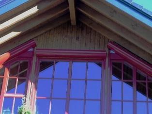Rundbohlenhaus mit roten Rolllädenkästen
