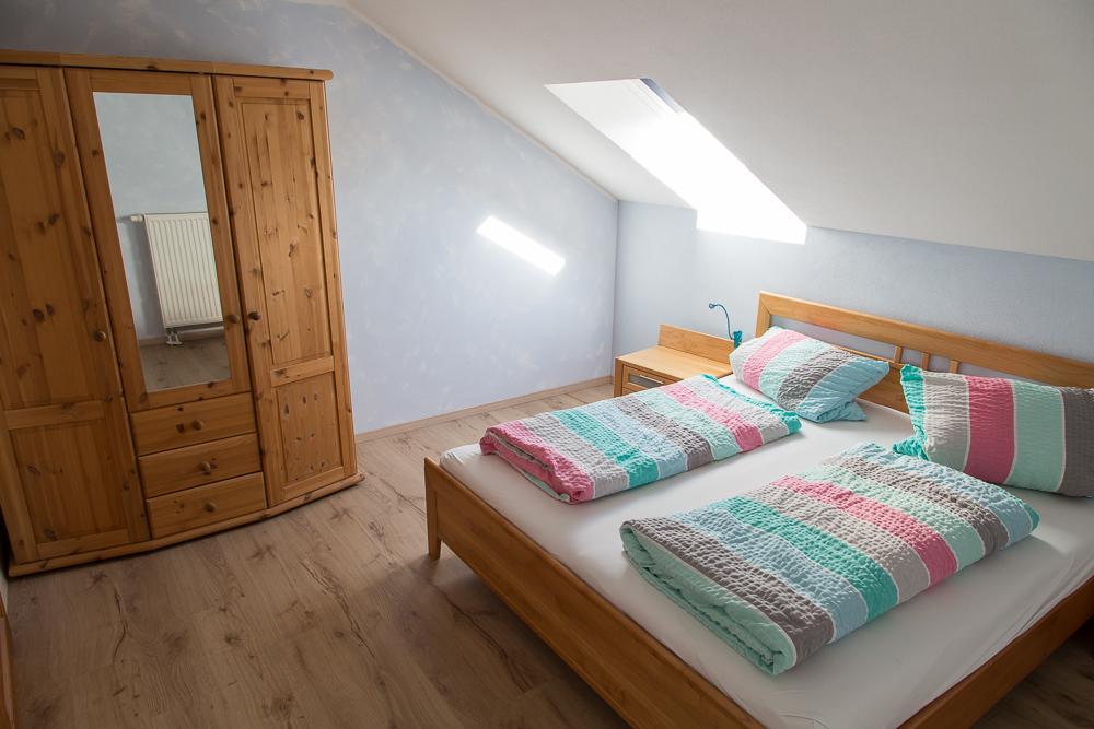 Schlafzimmer mit Doppelbett und großem Schrank