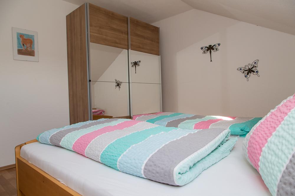 Zimmer mit Doppelbett und großem Spiegelschrank