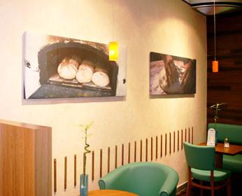 Das angeschlossene Cafe lädt zum Verweilen ein:<br />Die Wandfarbe ist komplementär zu den Sitzgruppen gewählt und wirkt ausgleichend. <br />Hier trinkt man gerne einen Capuccino mehr!