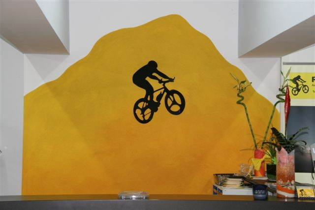 <b>Gestaltung, die begeistert: </b><br />Das ausgefallene Wanddekor unterstützt die Corporate Identity des Fahrrad-Fachgeschäfts, Struktur und Farblasuren sorgen für spannende Tiefenwirkung.