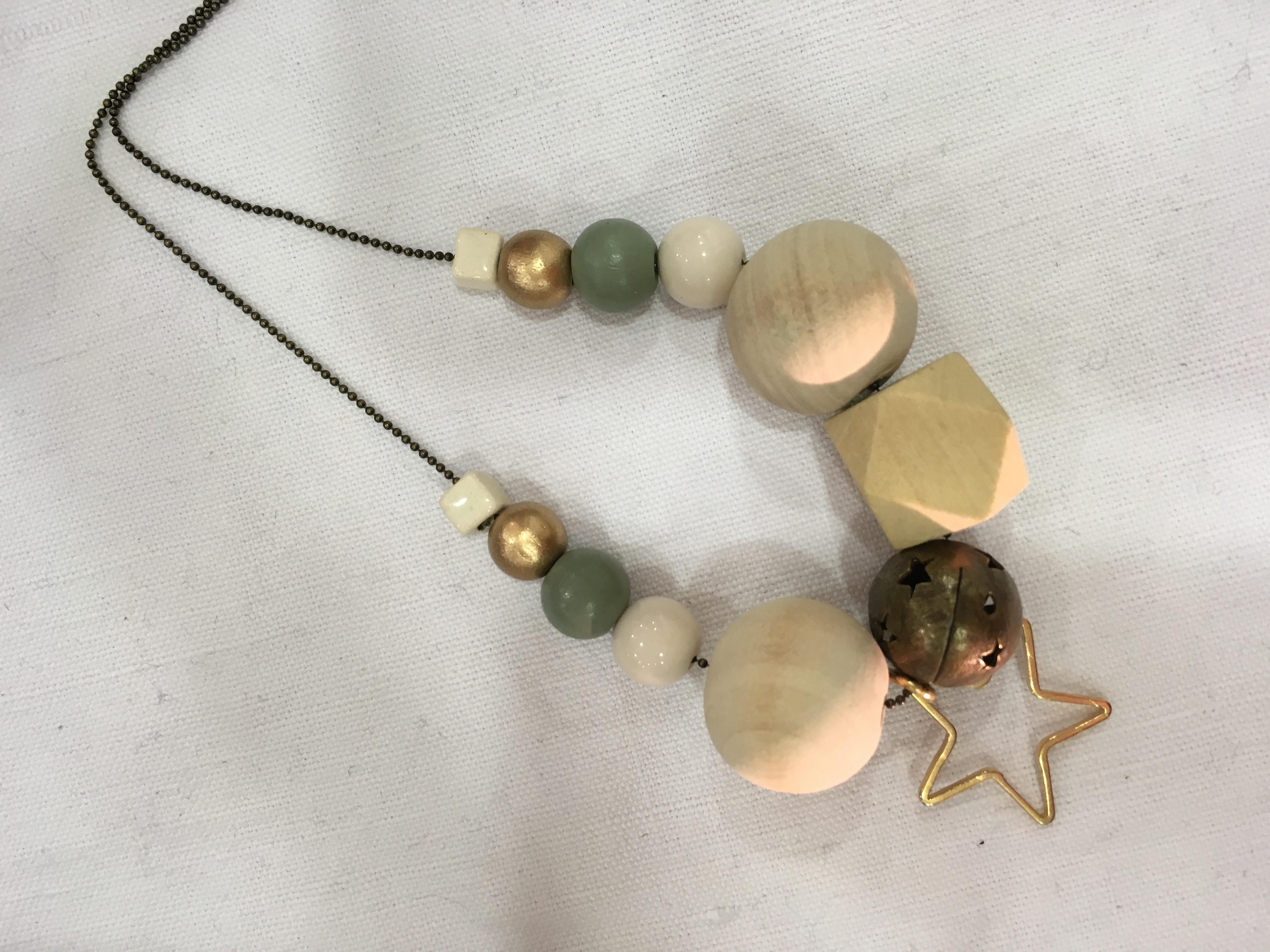 Sautoir composé de grosses perles en bois naturel, vert clair, en laiton et porcelaine, avec breloque étoile, le tout monté sur une chaîne à billes en laiton bronze
