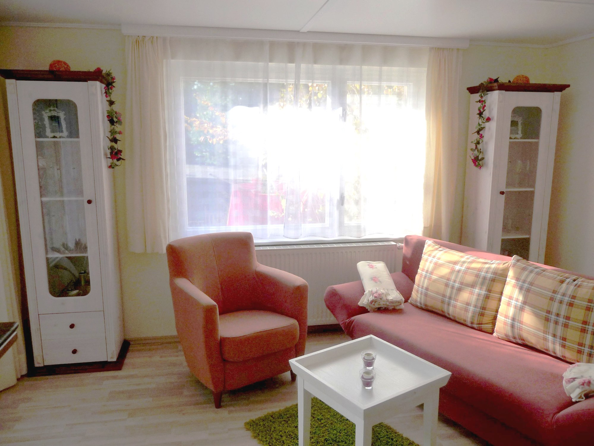 Die bequeme Sitzecke in warmen Terrakotta-Farben lädt nicht nur zum Verweilen  ein, sie bietet auch den Schlafplatz für zwei Personen. Lassen Sie auf der Couch die Seele baumeln und genießen Sie dabei den Blick über die Sonnenterrasse.