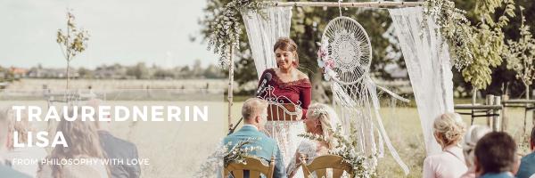 Hochzeitsrednerin Lisa Wötzel von Philosophy Love bei einer Trauung unter freiem Himmel mit Brautpaar, Traubogen und Hochzeitsgesellschaft. Sie spricht eine individuelle Hochzeitsrede.