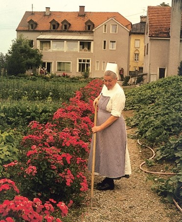 Das Kinderkrankenhaus von der Gartenseite im Jahr 1958. Die Laborschwester Ephrema bei der Gartenarbeit.