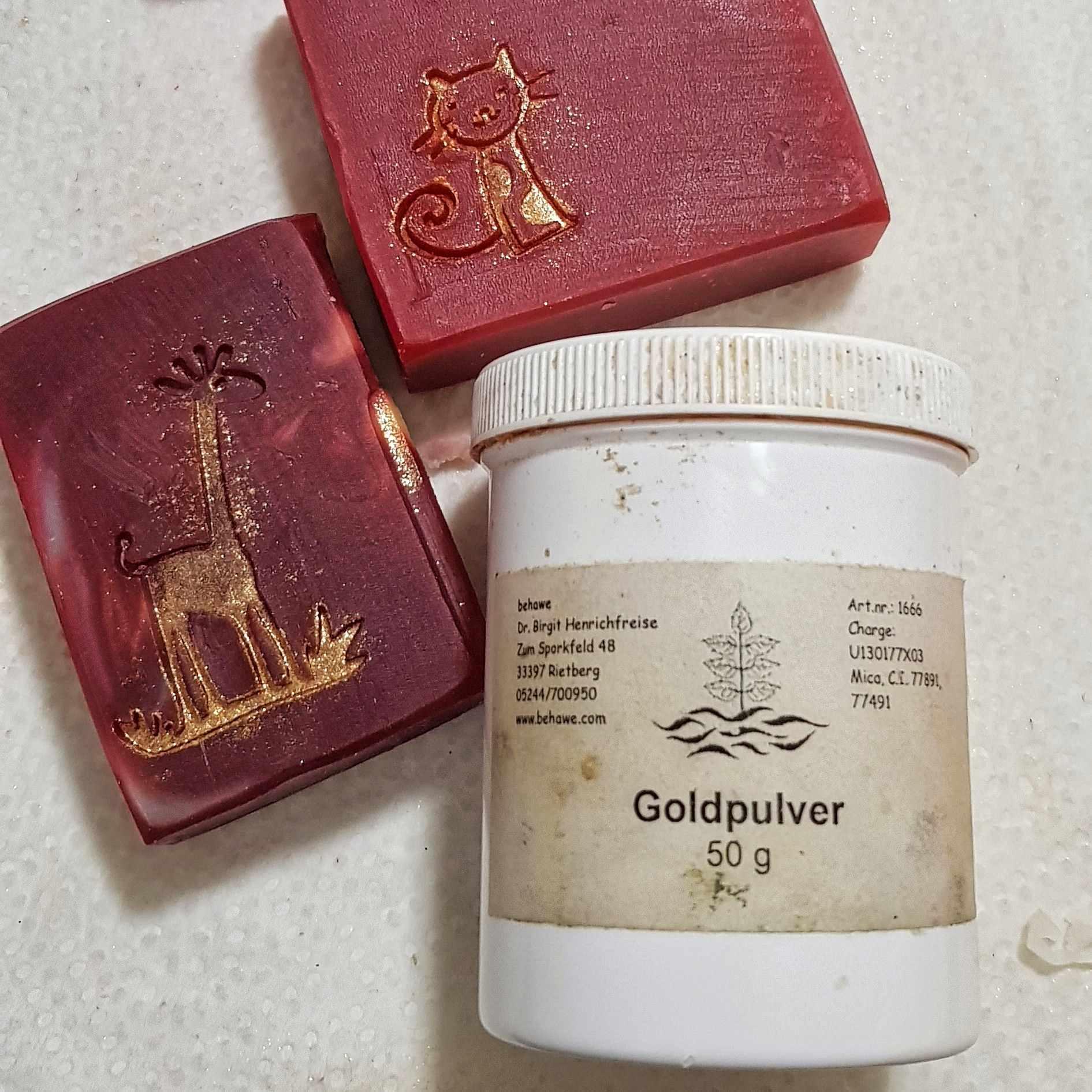 Der Stempel wird in farbiges oder goldenes Mica getaucht, bevor er auf das Seifenstück gedrückt wird.