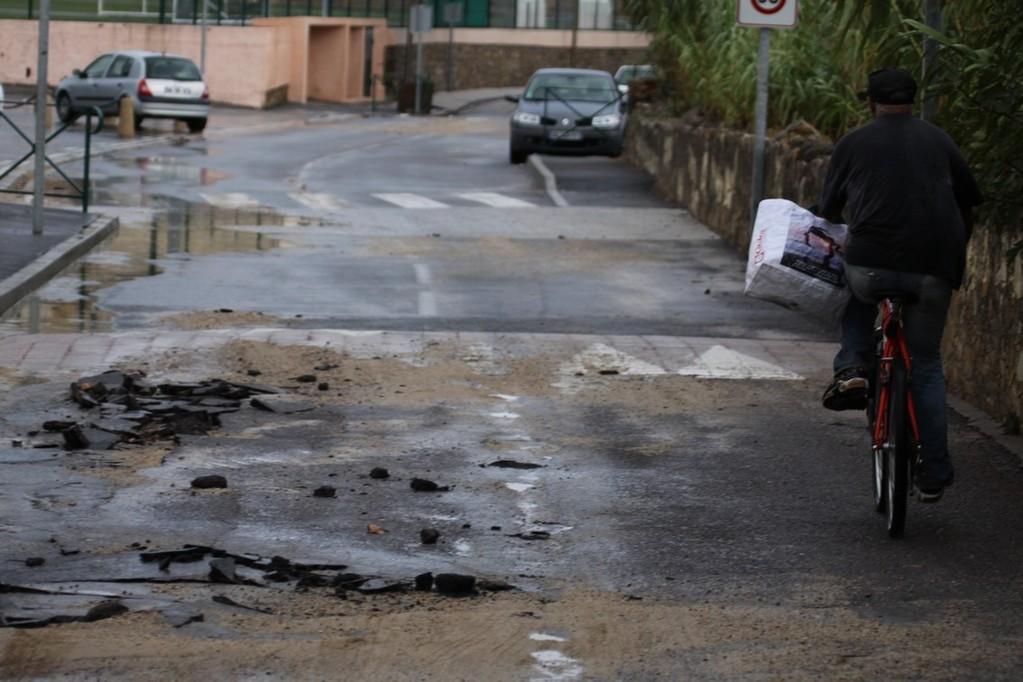 Le goudron de la route du collège emporté par les eaux.