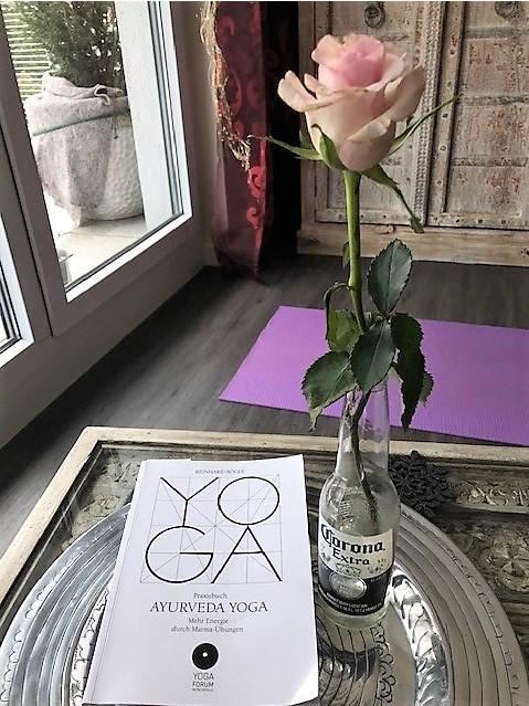 Gabriele Haage hält ein Buch hoch für ihr Programm Harmony Yoga meets Ayurveda