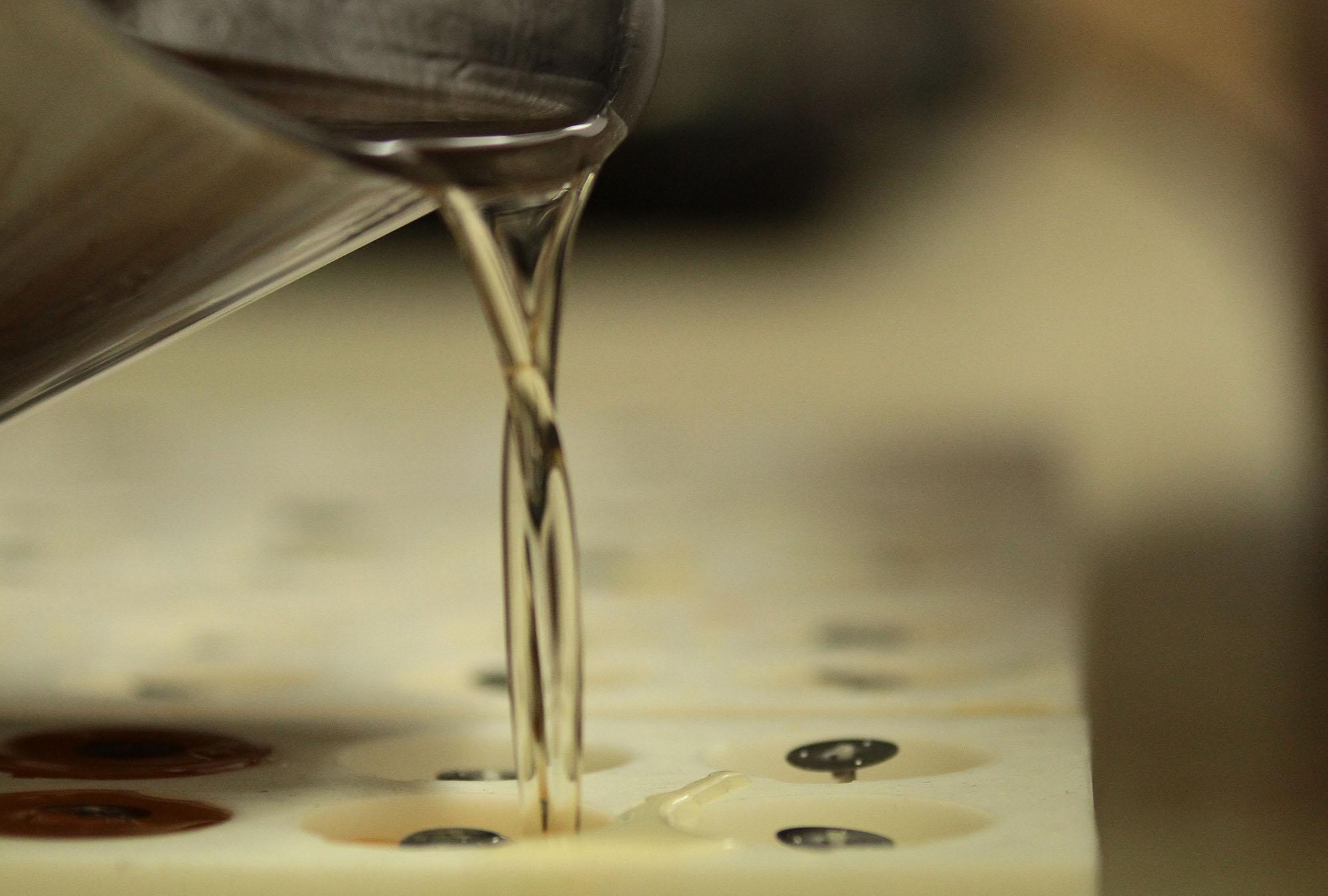 Nachdem die Dochte in die Form eingefügt wurden, kann das flüssige Wachs eingefüllt werden.