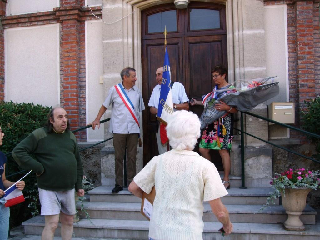 Départ de la mairie avec le drapeau des anciens combattants et la gerbe de fleurs