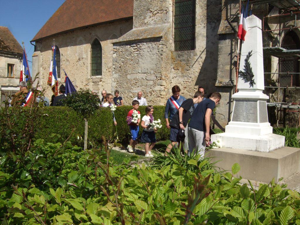 Ils sont accompagnés des enfants du village qui déposent à leur tour, un bouquet confectionné pour l'occasion par la Maire déléguée