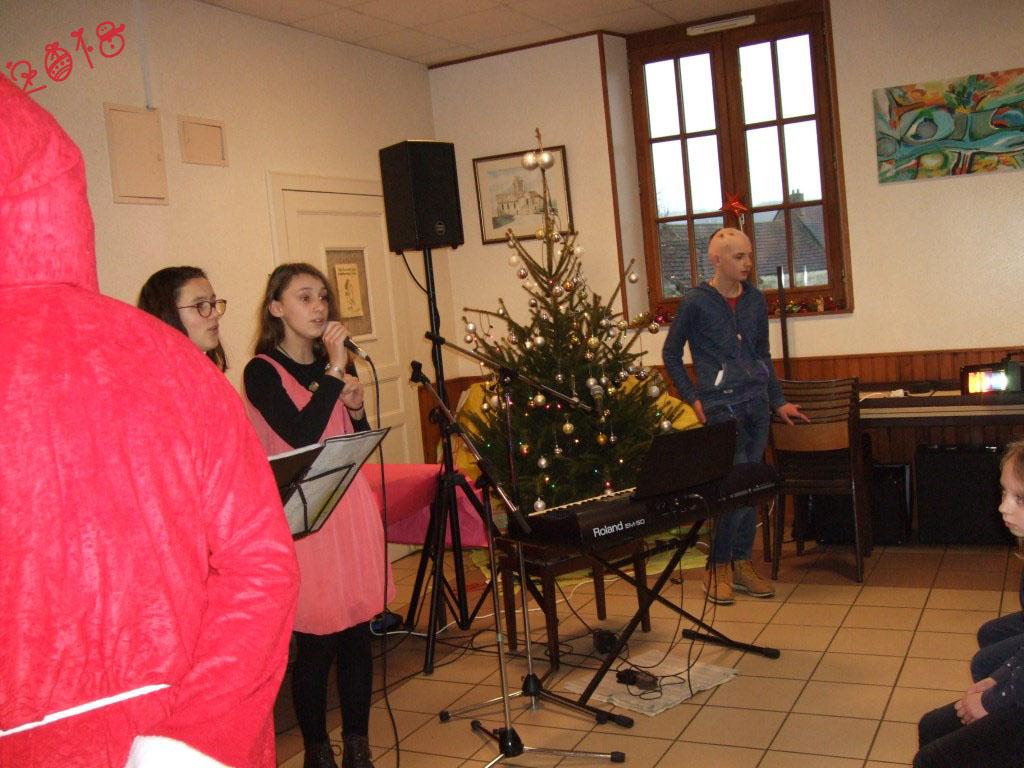 """Il est accueilli par Mélina & Anthéa qui interprètent (enfin) pour le bonheur de tous un chant de Noël """"Mon beau sapin"""""""