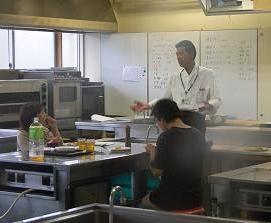 佐々木先生の調理した料理を試食される記者の方